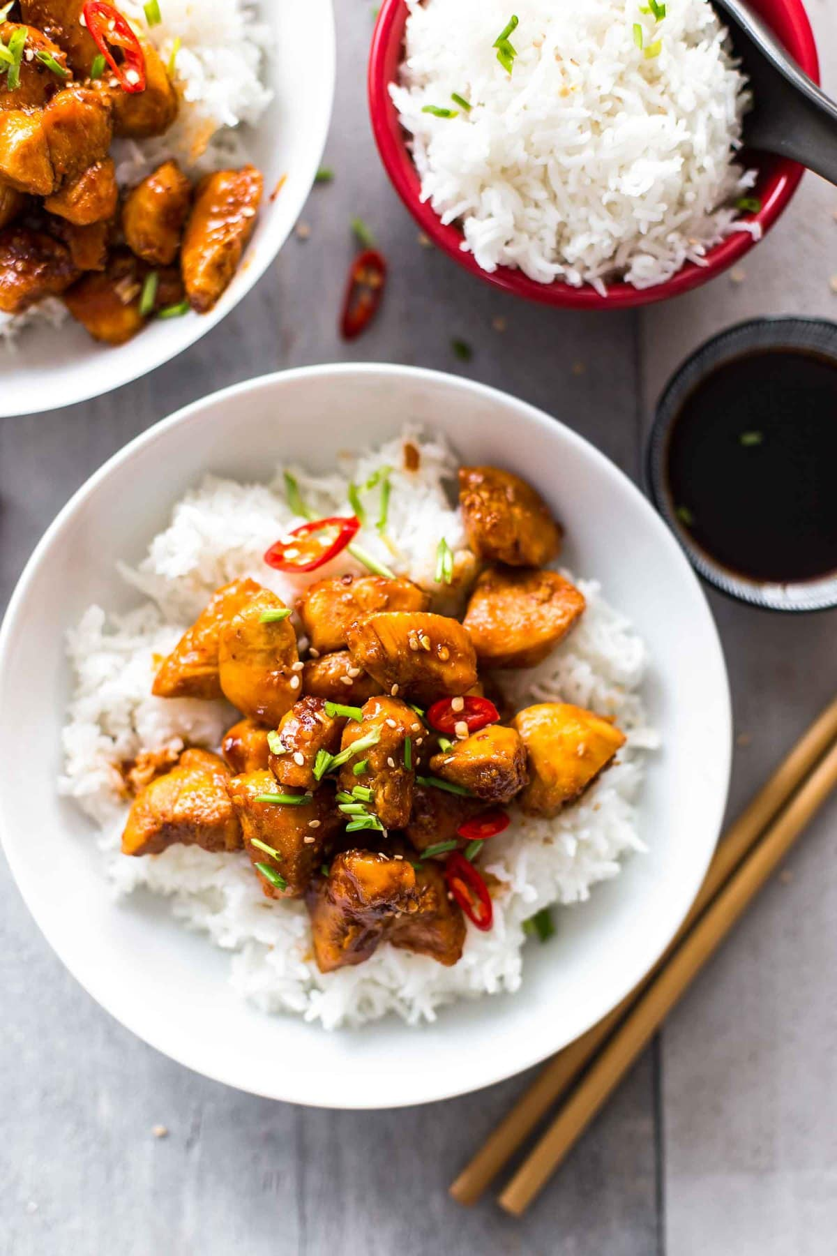 bowls of white rice and bourbon chicken on a table