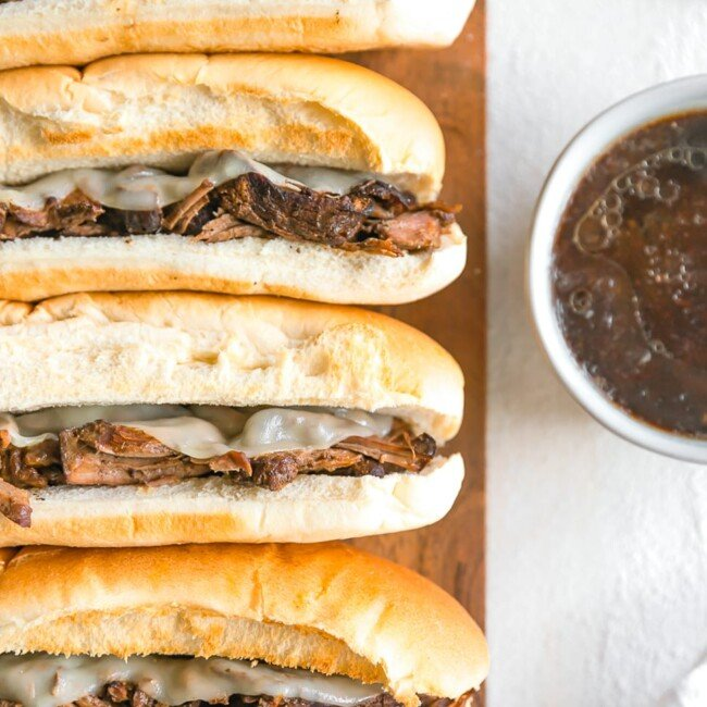 French Dip Sandwich, or French Dip Au Jus, is a delicious and easy way to enjoy crockpot beef! We create a Beef Au Jus sandwich with tender beef, provolone cheese, toasty bread, and of course the dipping sauce. Such a simple crockpot recipe that the entire family will love. This French Dip Sandwich Recipe is a winner!