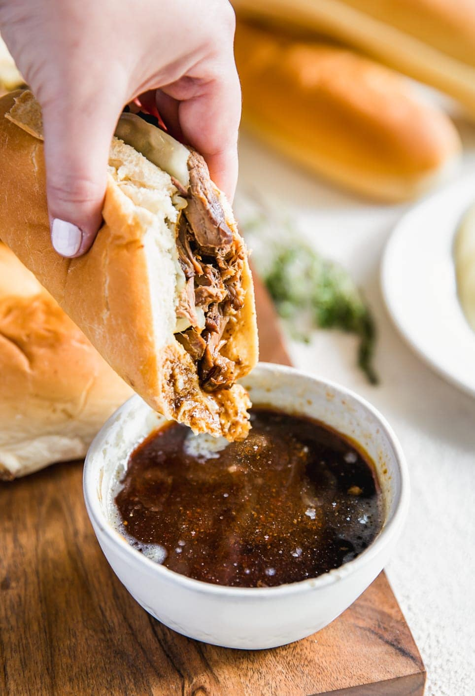 dipping french dip sandwich in beef au jus