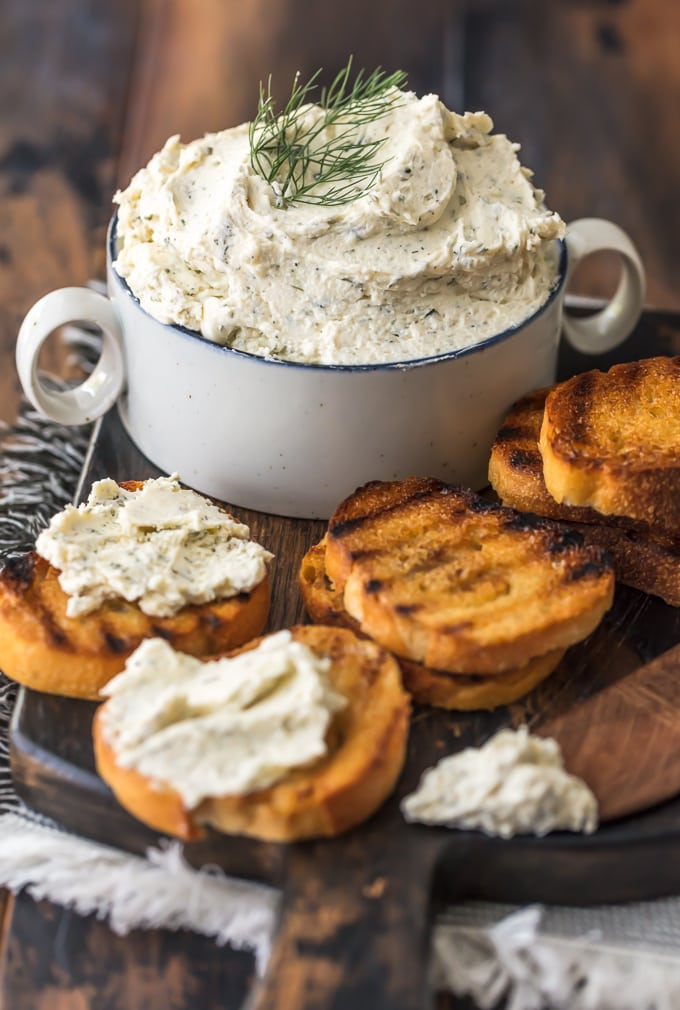 Boursin Cheese with toasted bread on a wood cutting board.