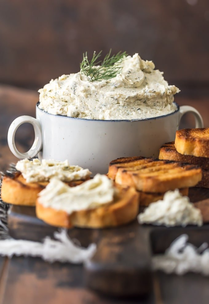 Stacked toasted bread surrounding a bowl of Boursin cheese.