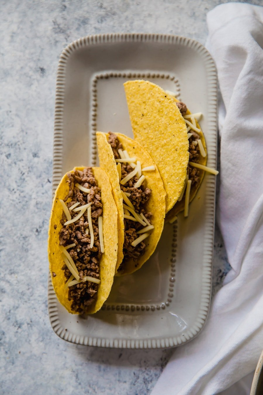 three taco shells filled with ground beef, on a white serving platter