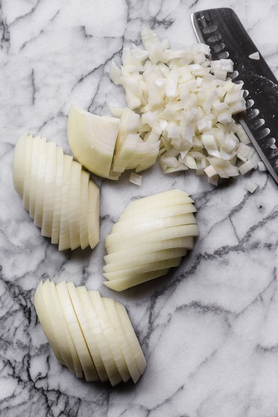 how to dice an onion: sliced onions on a marble surface, one quarter is diced