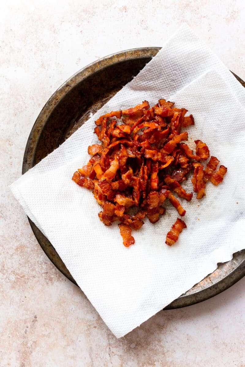 cooked bacon crumbles draining on paper towel
