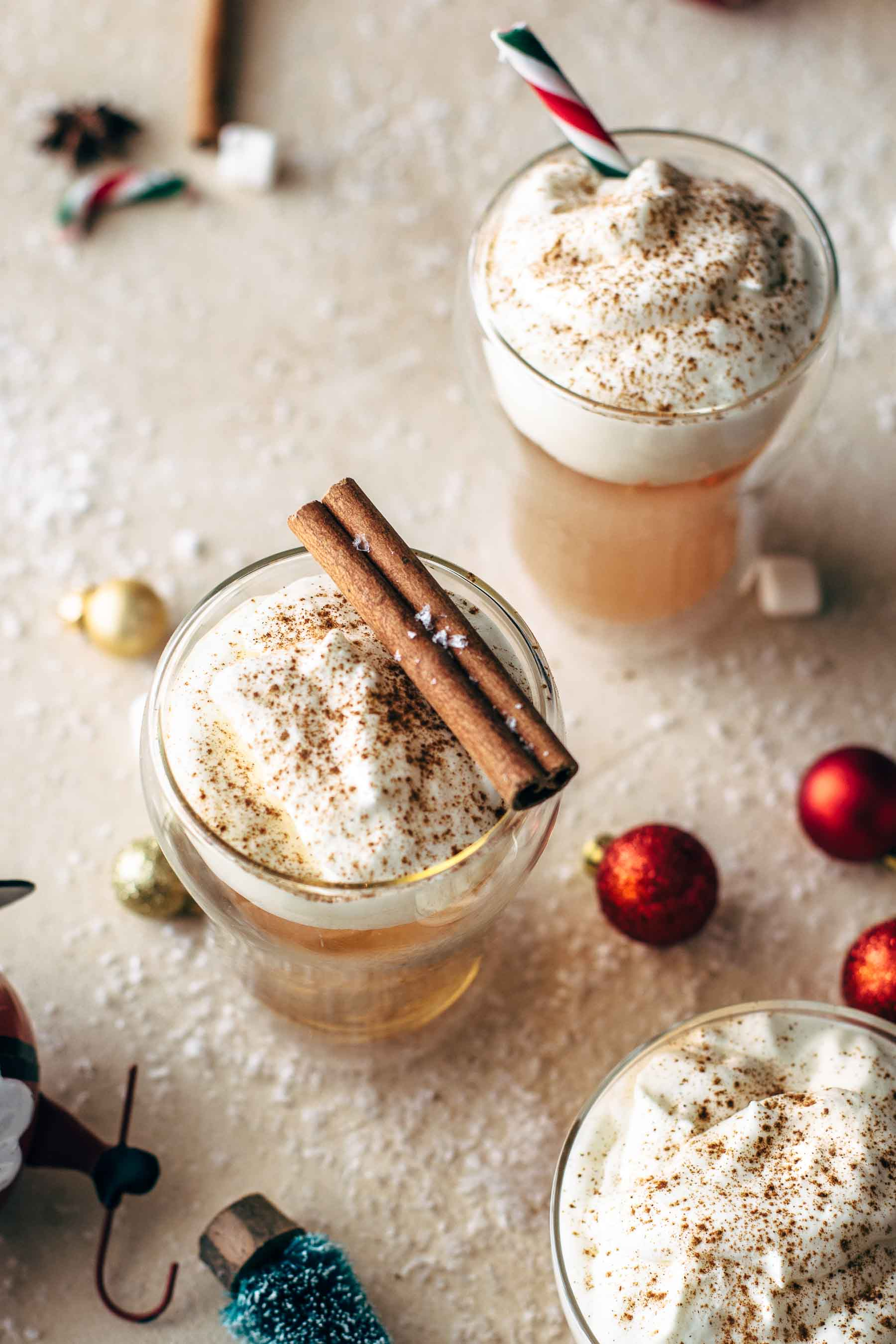 Caramel Apple Cider Hot Toddy in glasses, topped with whipped cream and cinnamon