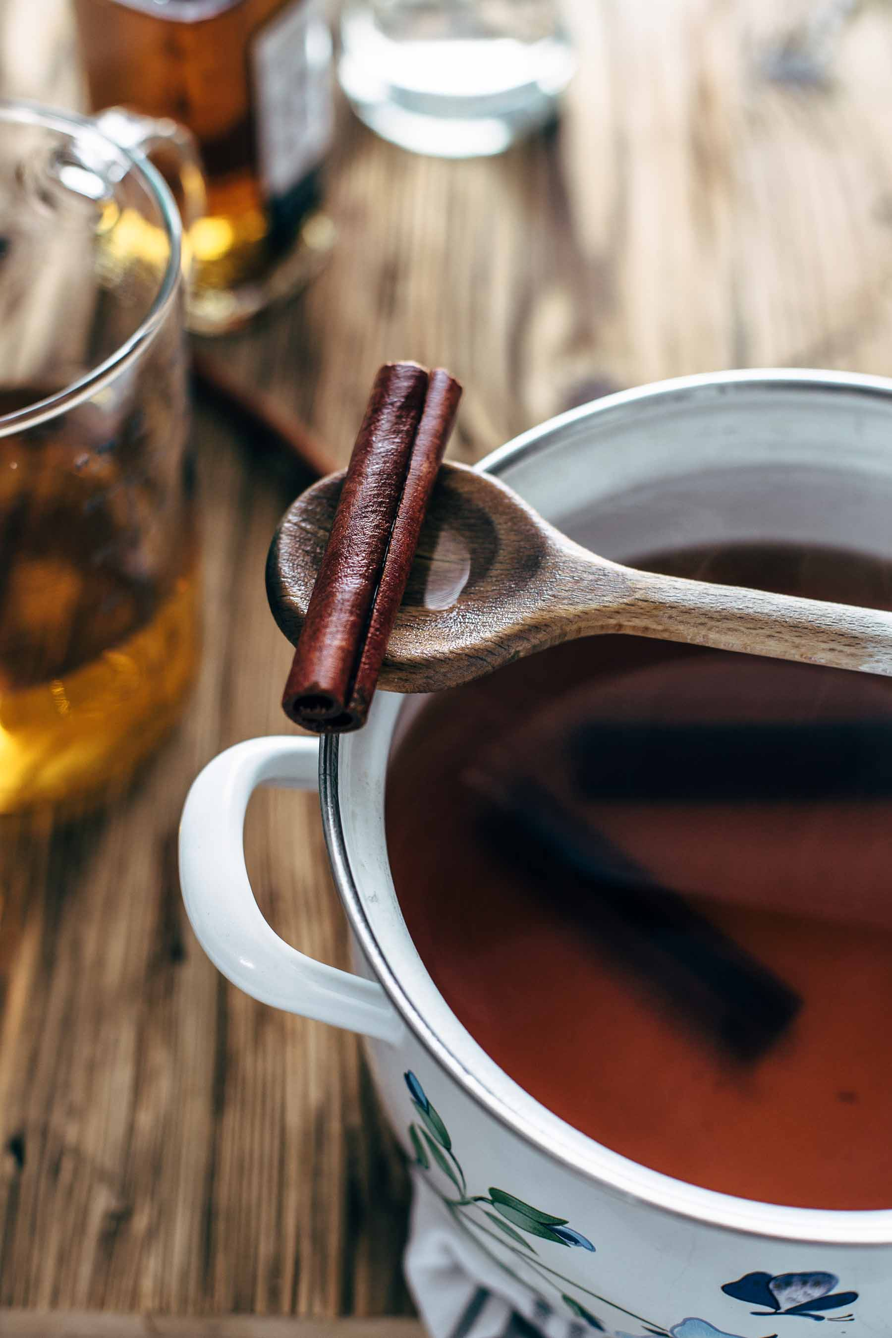A wooden spoon with a cinnamon stick, sitting on top of a pot of hot toddy beverage