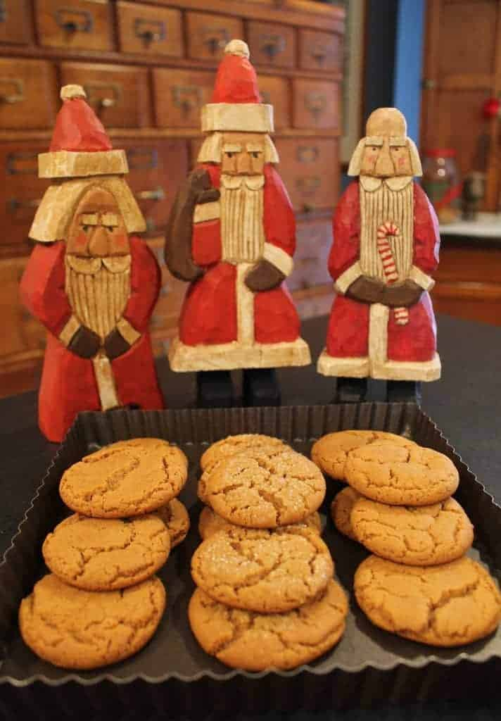 molasses cookies in front of Santa figurines