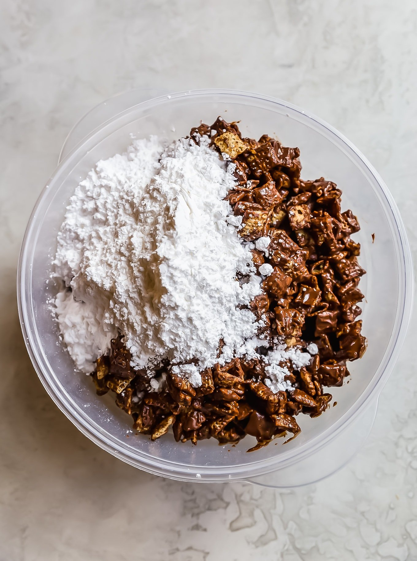 crispix cereal, chocolate, and powdered sugar in a mixing bowl