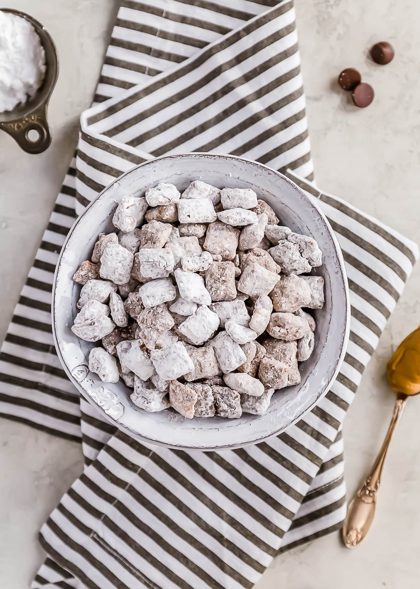a bowl of puppy chow sitting on a striped dish towel