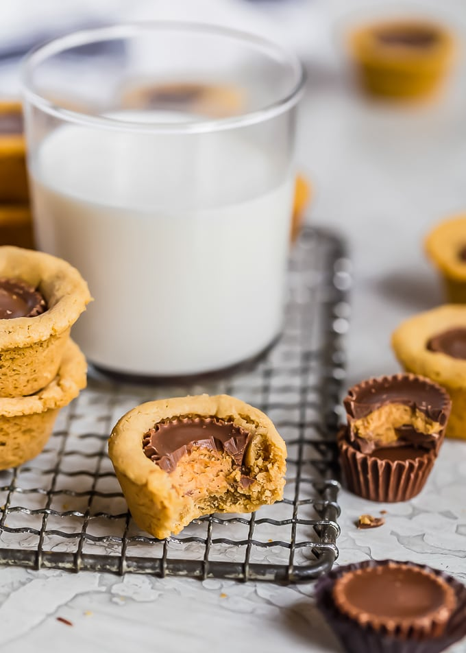 a glass of milk surrounded by peanut butter cups and cookies