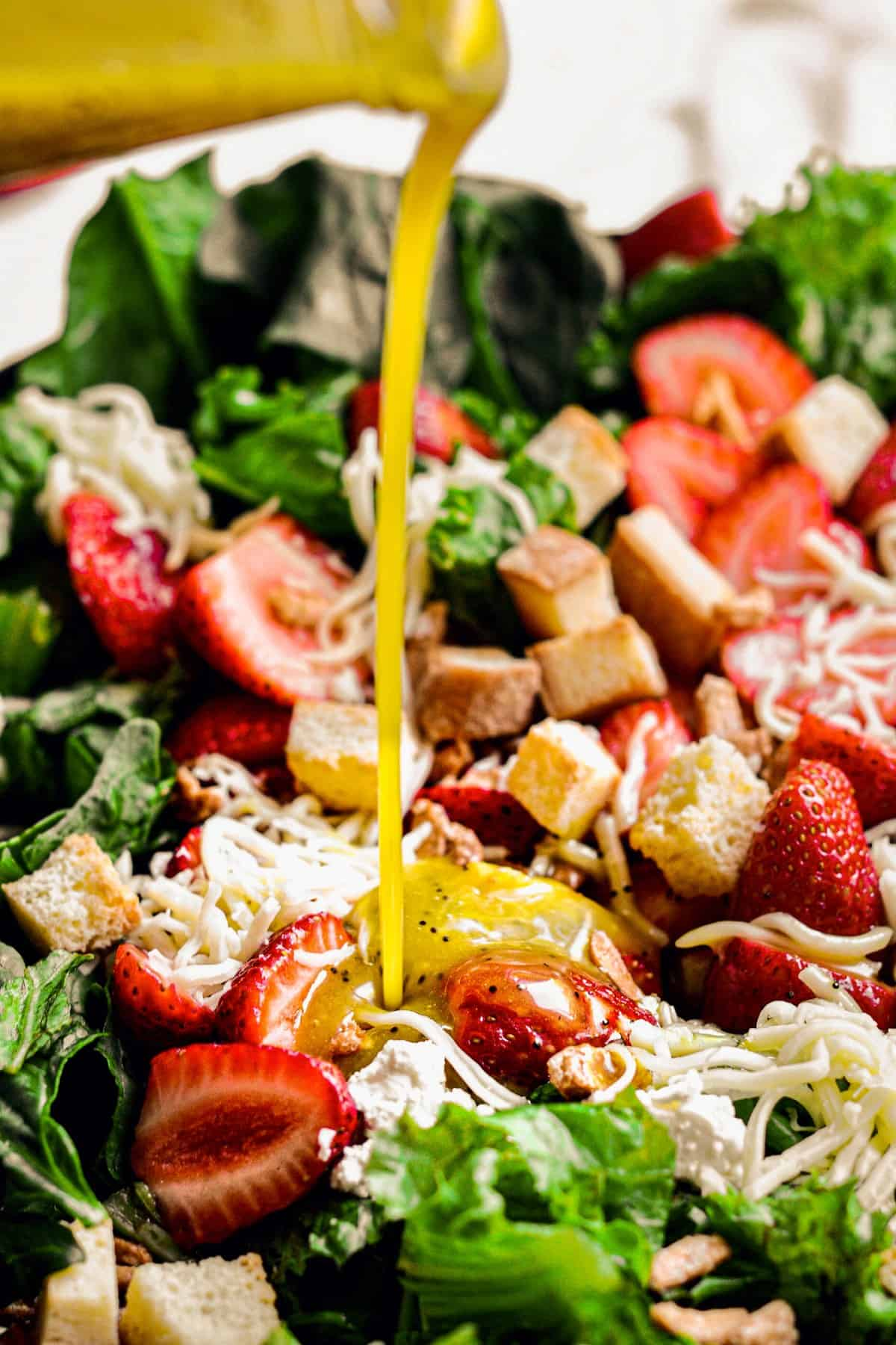 pouring salad dressing over a bed of greens and strawberries