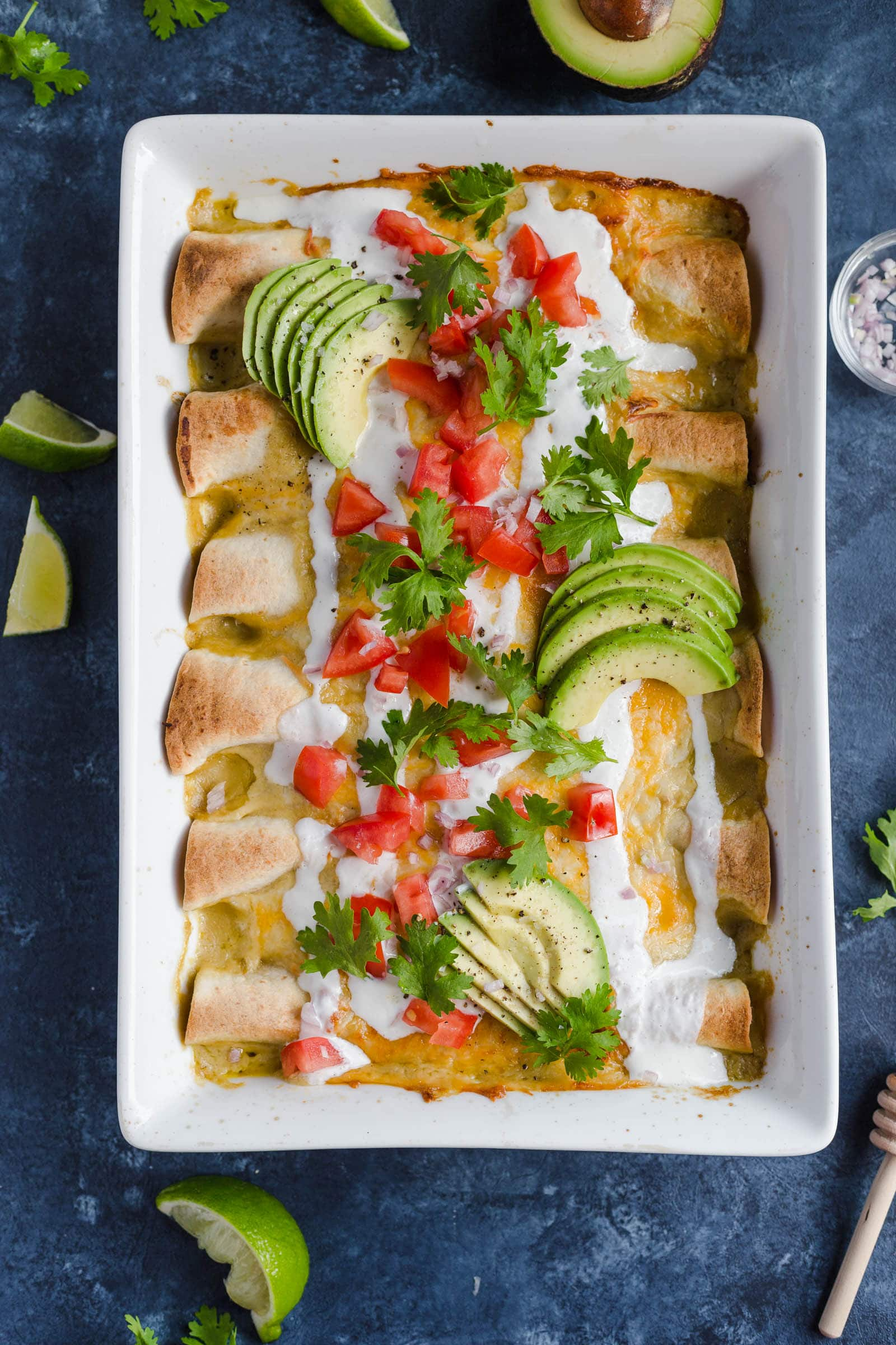 A baking dish full of easy chicken enchiladas made with cheese, sour cream, enchilada sauce, and more