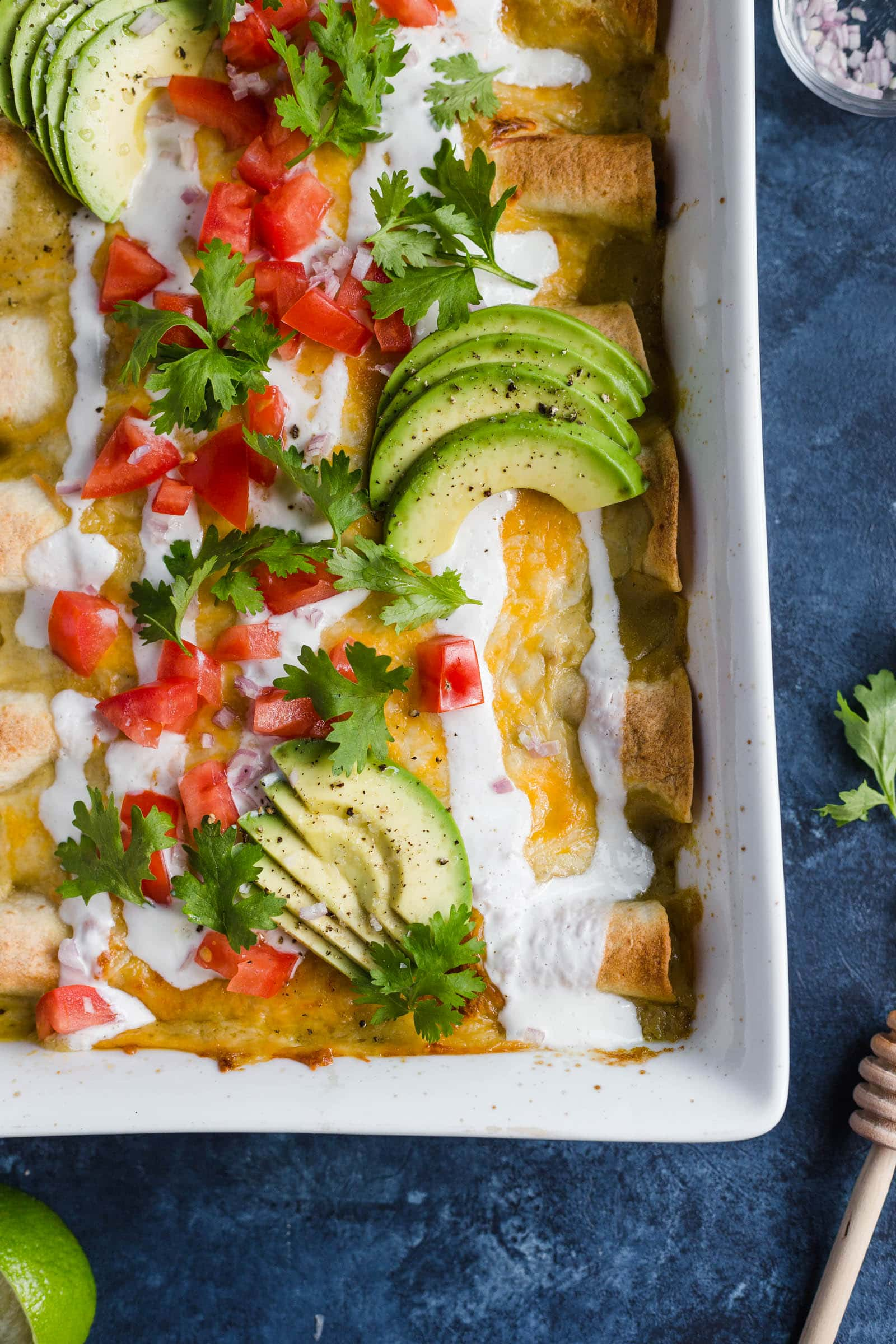 Honey Lime Chicken Enchiladas topped with avocado, tomatoes, and sour cream