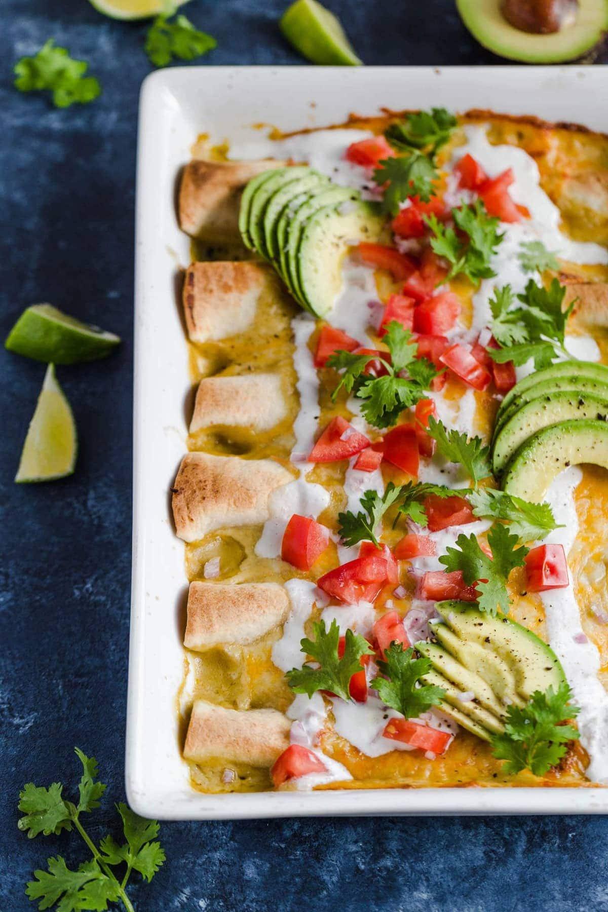 Honey Lime Chicken Enchiladas topped with tomatoes, avocado, sour cream, and cilantro