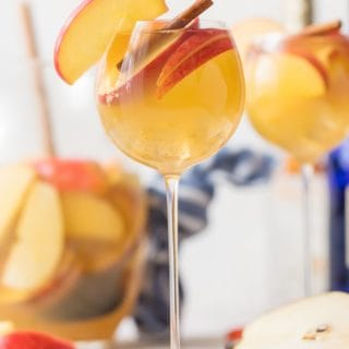 Apple Pie Sangria is a light, refreshing, delicious, and EASY Caramel Apple Sangria! This Fall Sangria Recipe is the hit of every party I take it to! Apple Pie Sangria is loaded with Apple Cider, Caramel Vodka, White Wine, Ginger Ale, and more! We call this Thanksgiving Sangria because it's Autumn in a glass. We have sangria recipes for every occasion, but this one is our favorite.