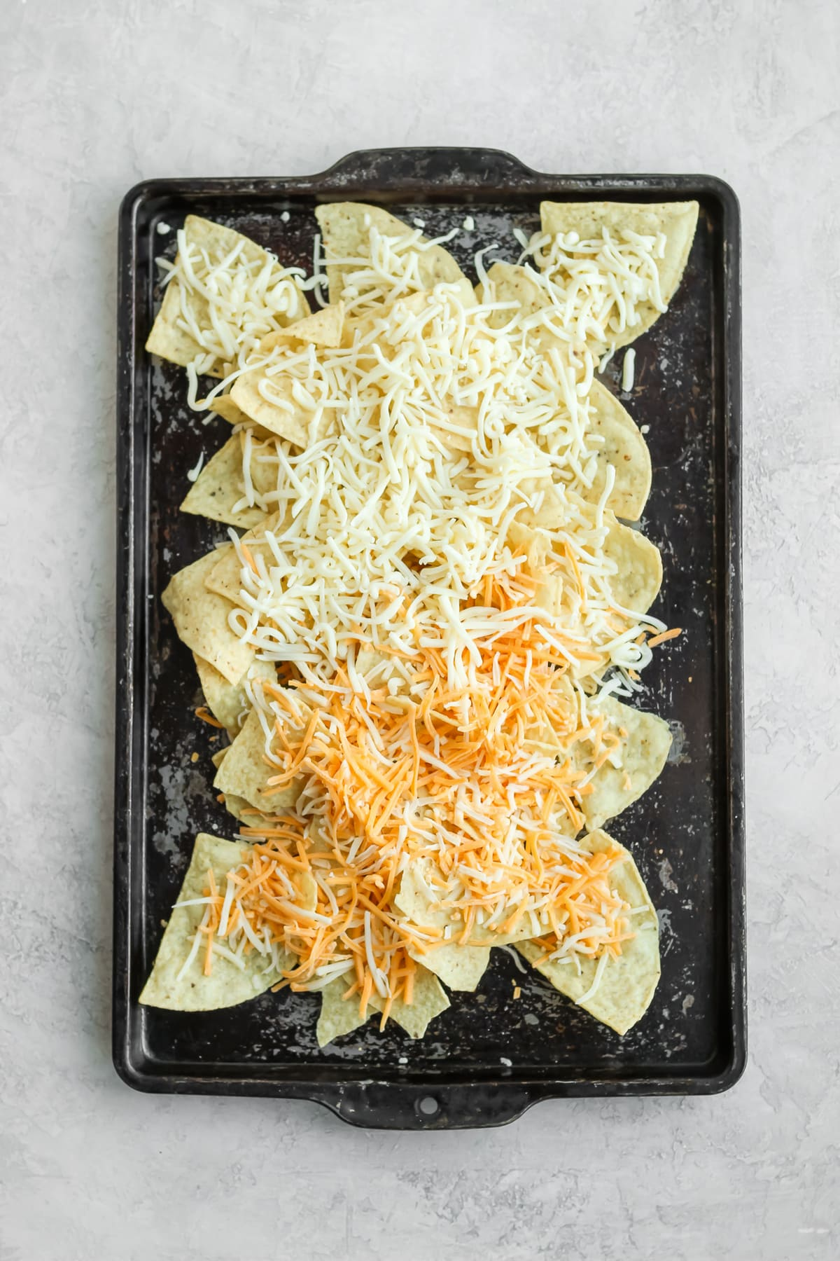 sheet pan of tortilla chips topped with shredded cheese