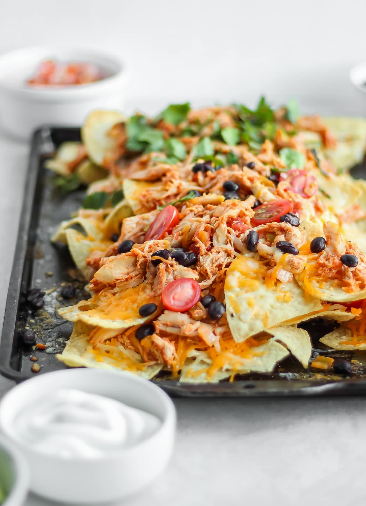 chicken nachos piled with beans, tomatoes, and more