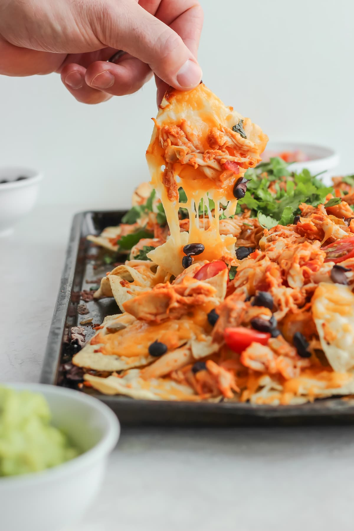 picking up a nacho from a sheet pan