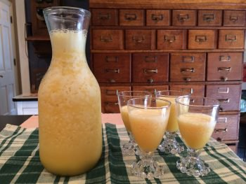 pitcher of blended orange juice with glasses full of orange juice next to it