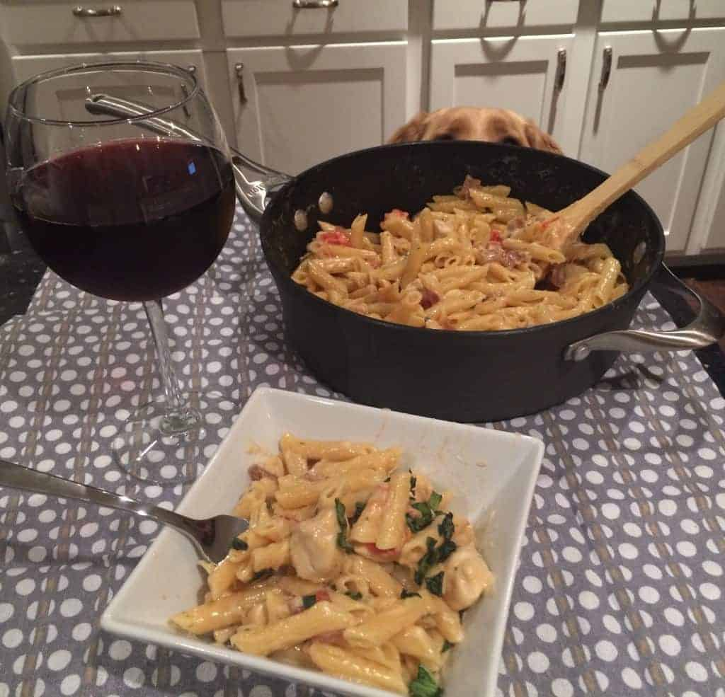 Plate of chicken alfredo with feta on table with wine and skillet and dog's eyes peering over skillet.