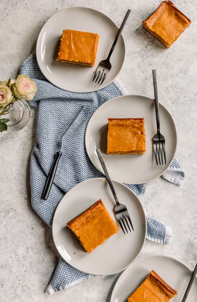 Three white plates with pumpkin gooey butter cake bars
