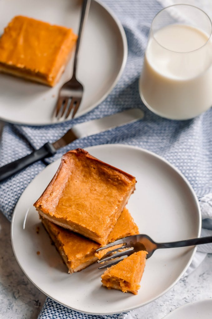 Pumpkin gooey butter cake on white plates, next to a glass of milk