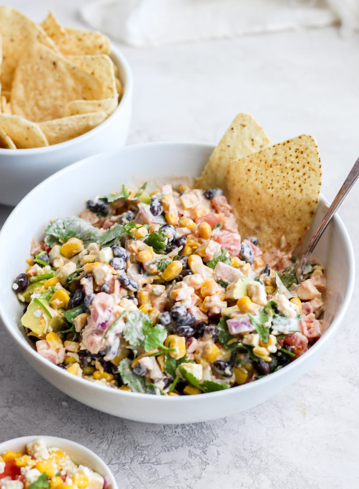 fiesta dip in a white bowl with two tortilla chips dipped in, next to a smaller bowl filled with chips