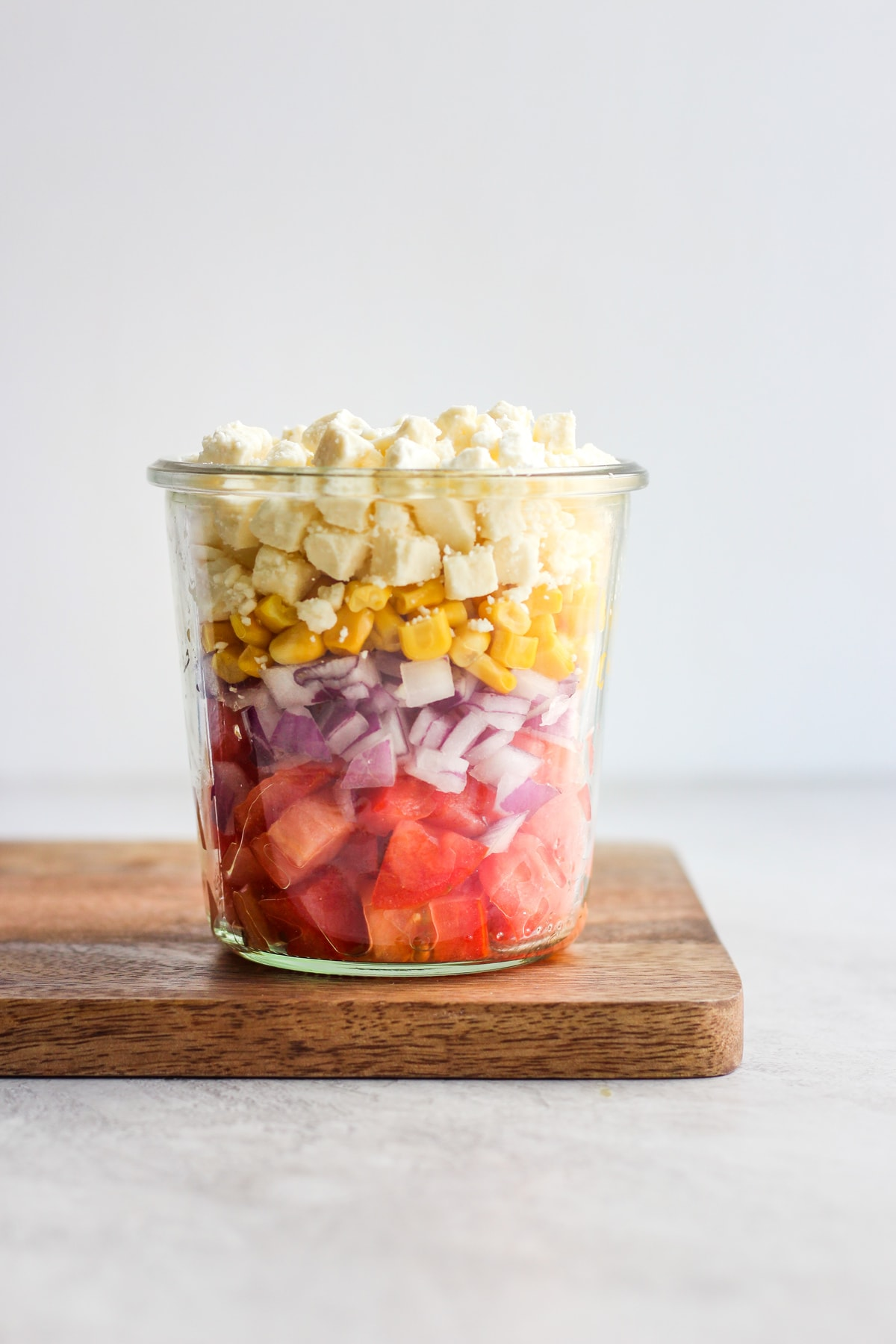 glass container filled with layers of tomatoes, onions, corn, and feta