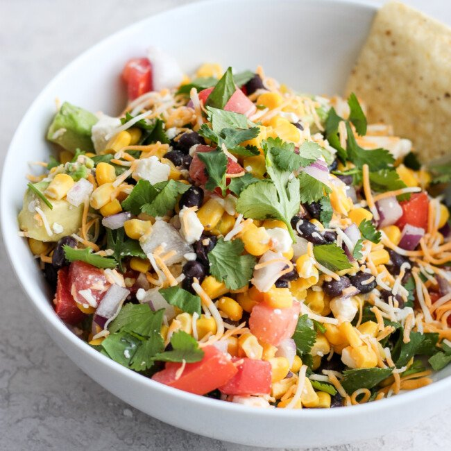 Mexican Dip is the perfect game day appetizer! This Mexican Dip recipe is filled with black beans, corn, feta, avocado, salsa, and so much more. It's crispy, fresh, and full of flavor! This Fresh Fiesta Dip will be a hit at any gathering. You could even turn this into a healthy fiesta salad!