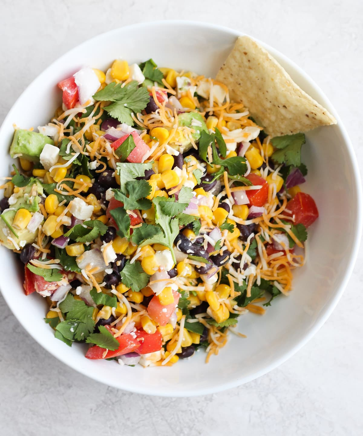 white bowl filled with cilantro, black beans, corn, feta, and more