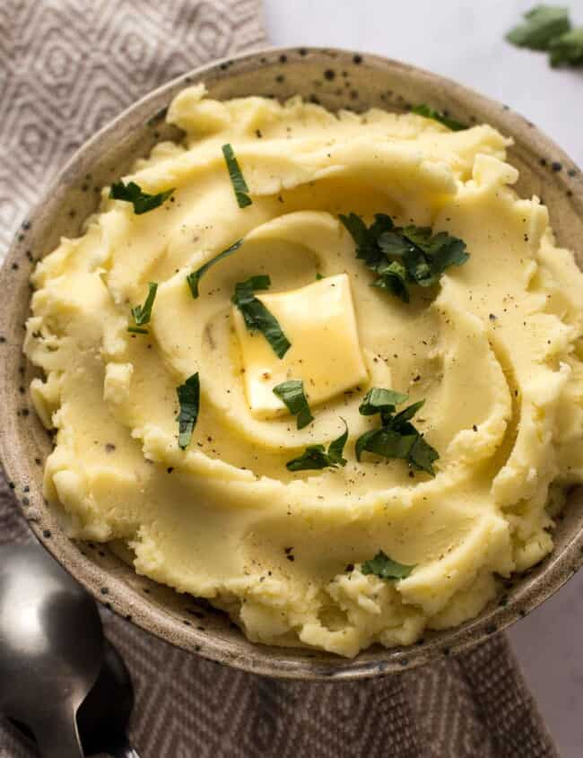 creamy mashed potatoes in a bowl topped with butter and parsley