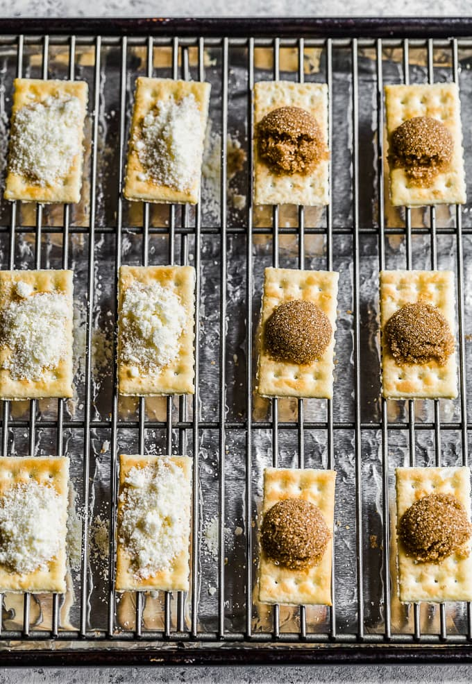 crackers lined up on a baking rack, topped with mounds of brown sugar and grated cheese