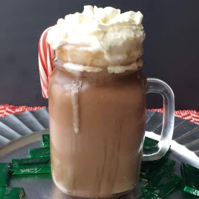 hot chocolate in a glass mug topped with whipped cream and a candy cane