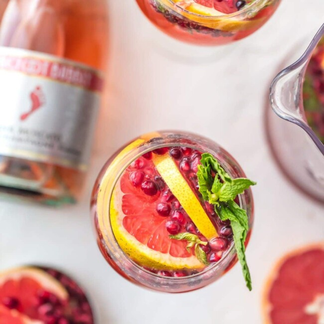 PINK CHAMPAGNE SANGRIA is the perfect New Years Eve cocktail! Ring in the new year with style and lots of pink bubbly. This fun sangria recipe is Pink Moscato Champagne mixed with grapefruit juice, pomegranate juice, and mint simple syrup. It's seriously delicious!