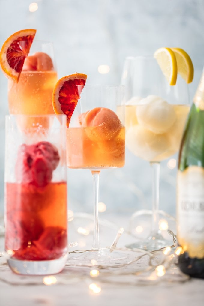 Glass of sherbet filled with champagne and garnished with slice citrus