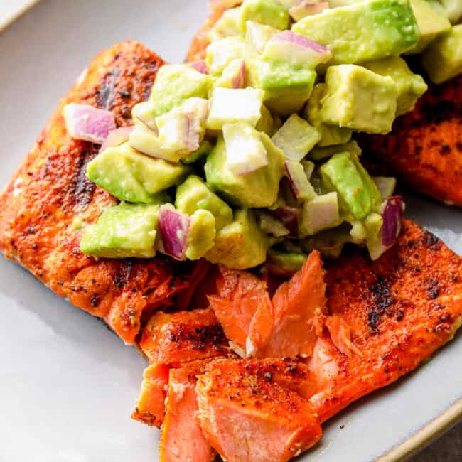 up close platter of grilled salmon with avocado salsa