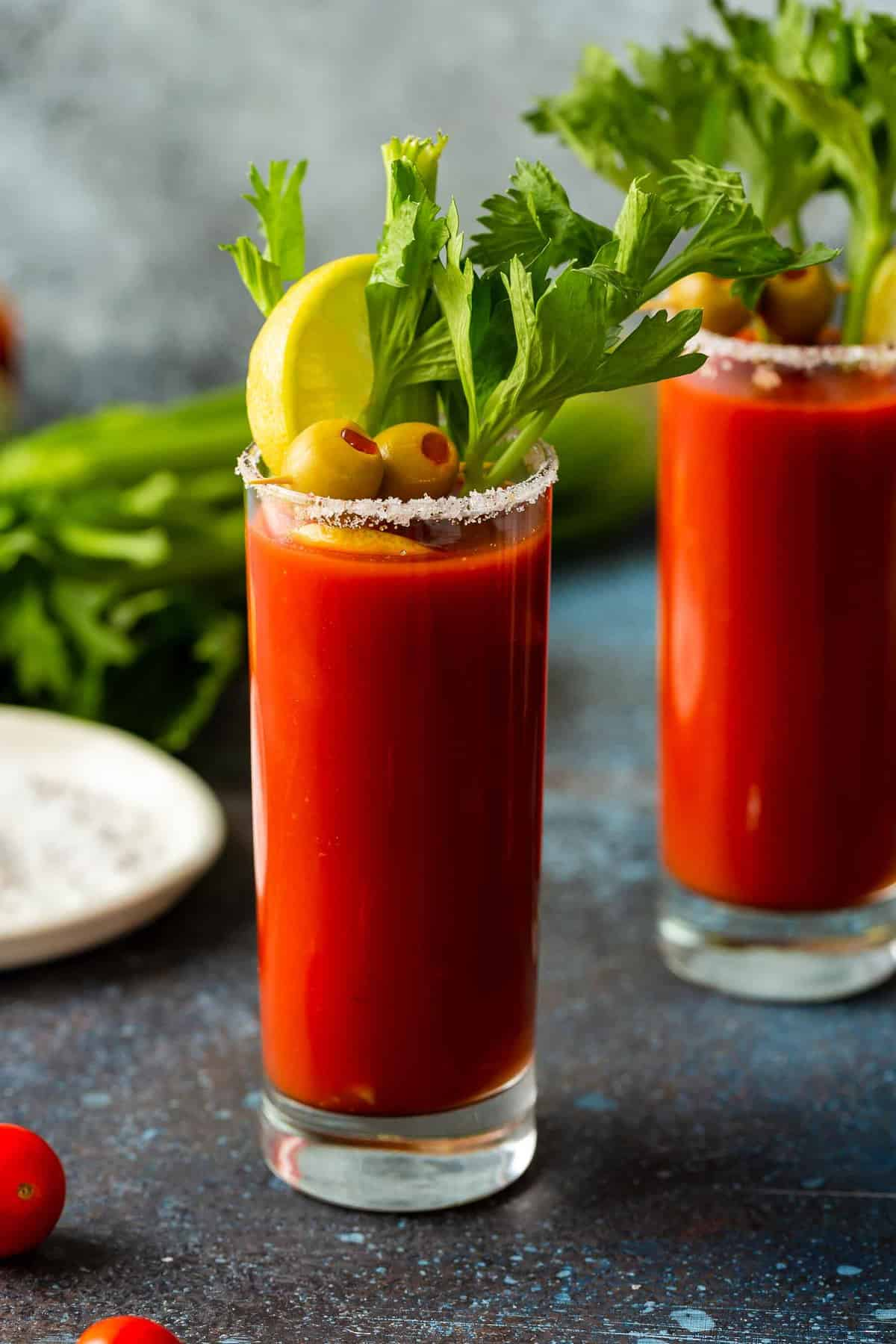 Two glasses of Bloody Mary with celery sticks.