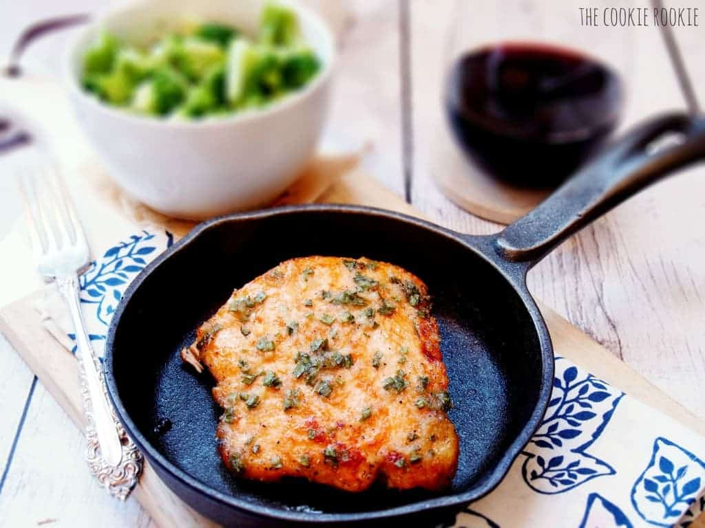 baked salmon in a skillet, next to a bowl of broccoli and a glass of wine