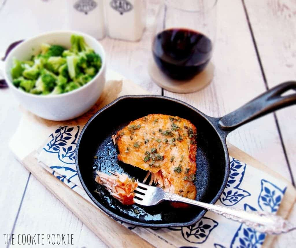 salmon in a skillet with a fork next to it, set on a table with broccoli and red wine