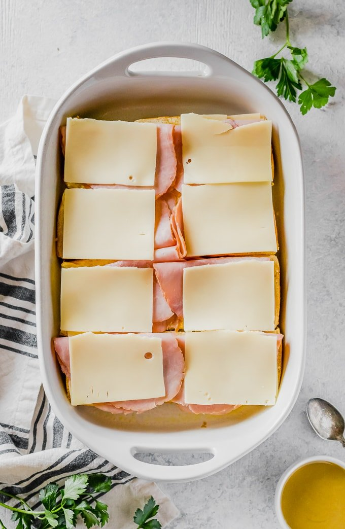 sliders topped with slices of ham and cheese in a baking dish