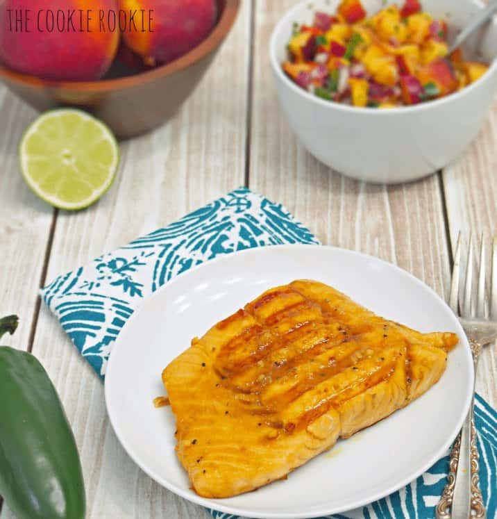 soy glazed salmon fillet on a white plate. on a table with a dish towel, a bowl of peaches, and a bowl of peach salsa