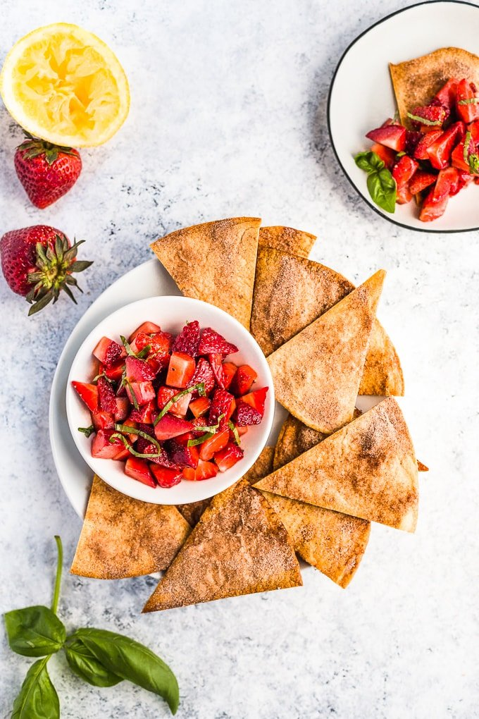 A plate of cinnamon chips with a bowl of strawberry fruit salsa