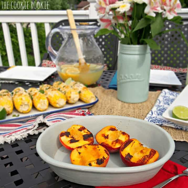 Grilled peach halves in a bowl, served outside.