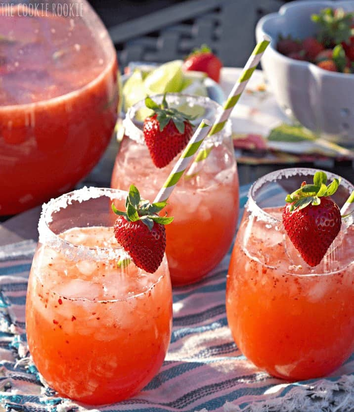 three glasses of margarita punch with strawberry garnish