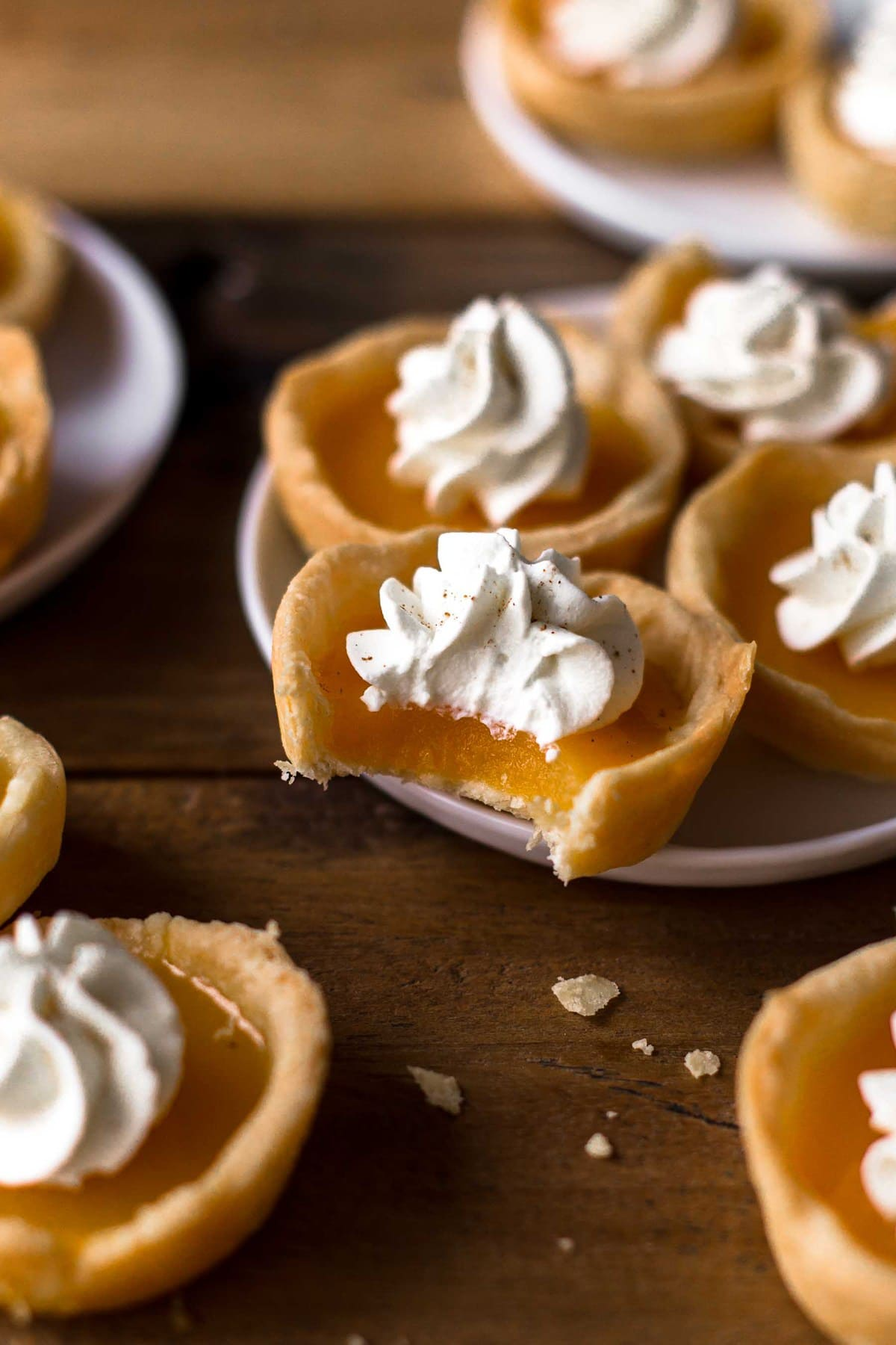mini pumpkin pie shots on plates, one has a bite taken out of it