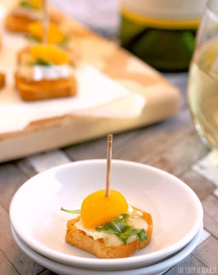 single mini apricot brie bite on a white plate