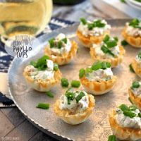 phyllo cups topped with green onions on silver platter