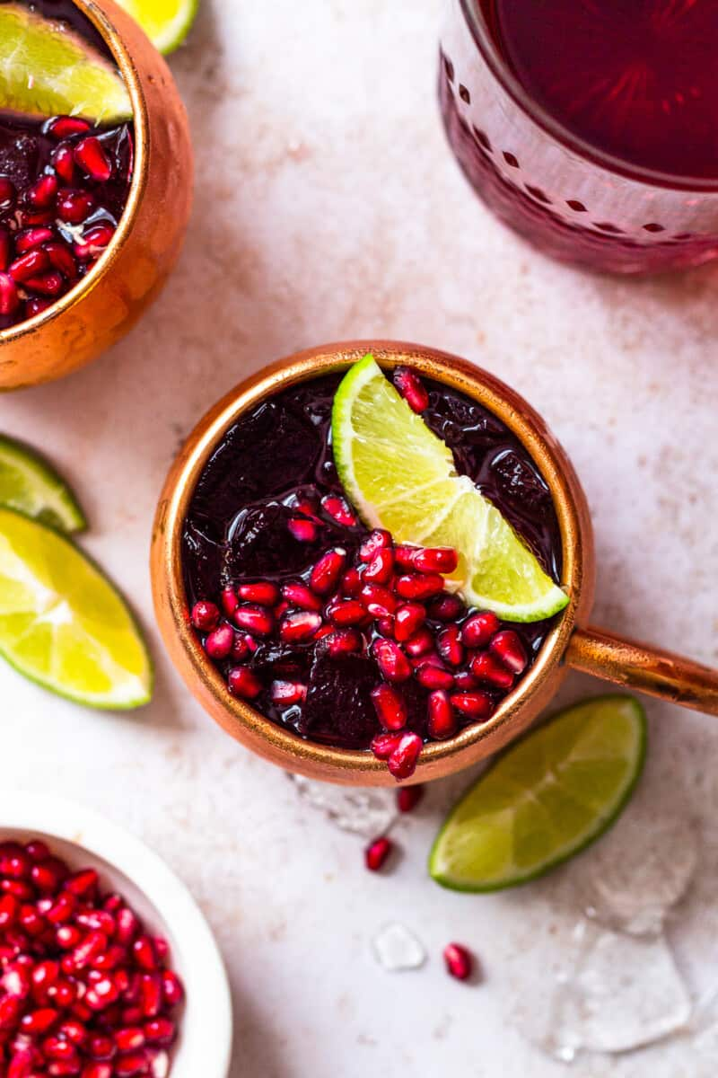 overhead pomegranate moscow mules garnished with limes and pomegranate seeds