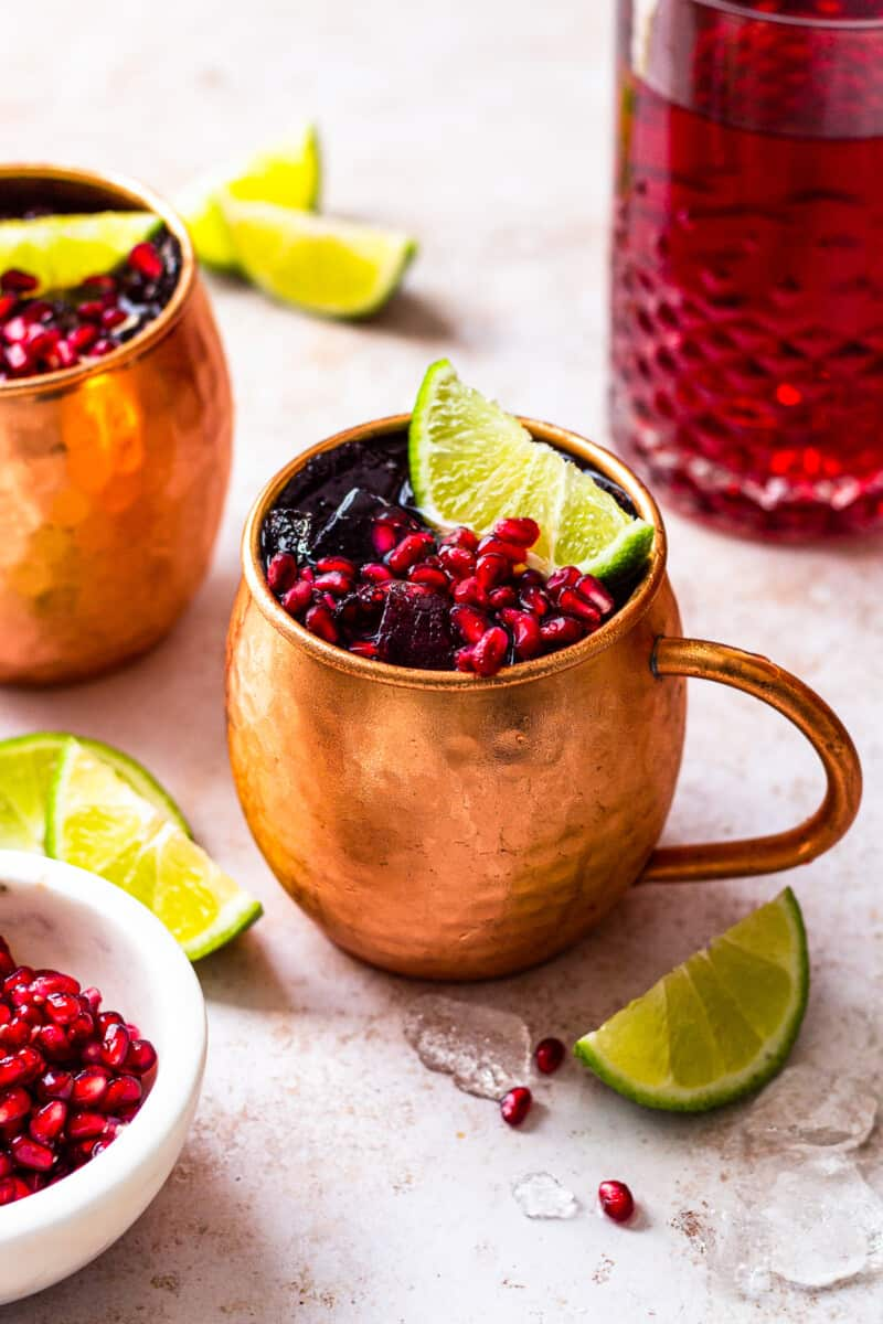 pomegranate moscow mules garnished with limes and pomegranate seeds