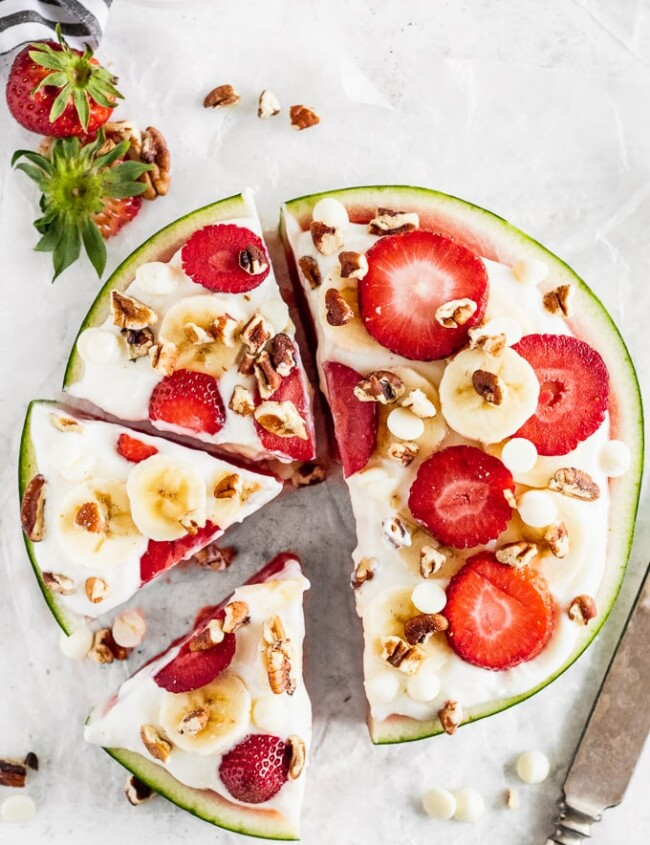 Watermelon Pizza is a delicious and fun sweet treat that everyone will enjoy! Juicy watermelon topped with a low-fat cheesecake sauce, fresh strawberries, bananas, white chocolate chips, and pecans is the ultimate (but still indulgent) healthy dessert. This refreshing cheesecake watermelon pizza is an easy summer dessert you'll be eating all season long!